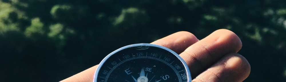 Person's hand holding a compass pointing South East